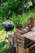A garden kitchen with a round grill in a summer garden
