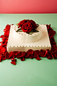A wedding cake decorated with silver pearls and rose petals