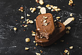 Two chocolate ice cream stick with hazelnuts