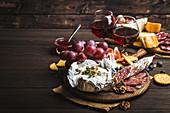Platte mit Käse, Wurst, Crackern, Brot, Trauben und Nüssen dazu Rotwein