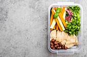 A healthy lunchbox with chicken breast, nuts, salad and vegetables sticks