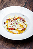 Plate of saffron risotto with chorizo sausage and parmesan shavings