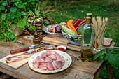 Ingredients for barbecue skewers with pork, bacon and vegetables on a wooden table in a garden