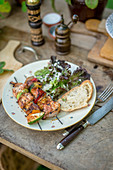 Grilled meat and vegetable skewers with salad and bread