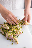 Raw chicken being rubbed with a peppermint, garlic, lemon and pistachio nut marinade