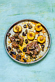 Duck breast with caramelized peaches and mushrooms on a round tray