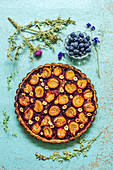 Pie with plums and hazelnuts on a blue background with herbarium and fresh blueberries