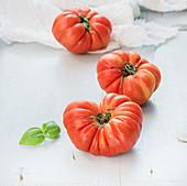 Fresh ripe heirloom tomatoes and basil leaves