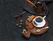 Tasse schwarzer Kaffee mit Schokoladenkeksen, Zimtstangen und Rohrzuckerwürfeln