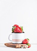 Fresh ripe red strawberries in country style enamel mug