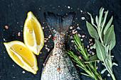 Doraden-Fischschwanz, Zitronen und Kräuter auf schwarzer Schieferplatte