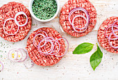 Raw ground beef meat cutlet for cooking burgers with onion rings and spices