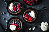 Chocolate Dutch babies with berries in cast-iron pans