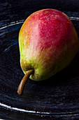 A pear on a black wooden plate