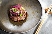Japanese-style beef medallions with spring onions and red amaranth shoots