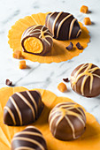 Chocolate pralines filled with caramel on a marble background