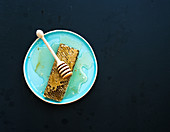 Honeycomb with honey dipper on blue ceramic plate over black background, top view copy space