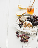 Camembert cheese with grape, walnuts, pear and honey on vintage metal plate over white rustic wood backdrop