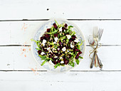 Beetroot salad with arugula, feta cheese and pumpkin seeds in vintage plate over white rustic wooden background
