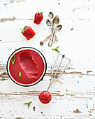 Strawberry sorbet or ice-cream with fresh berries, mint and metal scooper on over white rustic wooden backdrop