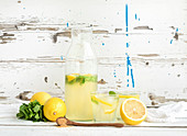 Fresh homemade lemonade with lemons and mint on white wooden backdrop