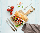 Tomato, mozzarella and basil sandwich on wooden chopping board over light blue background