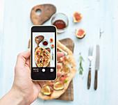 Hausgemachte Pizza wird mit Smartphone fotografiert