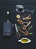 Grilled lamb chops. Rack of Lamb with garlic, rosemary and spices on slate tray, wine glass, oil in a saucer and bottle over black wood background