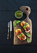 Tomato, mozzarella and basil sandwiches on dark wooden chopping board, pesto jar, dinnerware over black background
