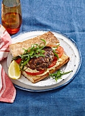 Burger mit Lammhack-Pattie und Tomaten im Fladenbrot