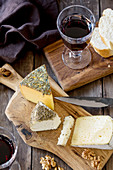 A cheese platter with bread, walnuts and red wine