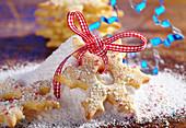 Eiskristalle aus Mürbteig mit bunten Zuckerperlen und Puderzucker