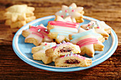 Colourful star biscuits with icing and filled with jam