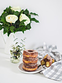Doughnuts with cinnamon sugar, stacked on a plate and on a tea towel
