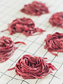 Homemade raw beetroot tagliatelle nests on a cloth