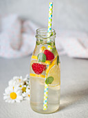 Elderflower lemonade served with fruit in a glass bottle