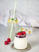 Elderflower panna cotta served with raspberry sauce and raspberries