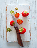 Strawberries, partially prepared with a kitchen knife on a wooden board