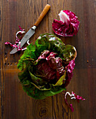 Fresh radicchio salad with a kitchen knife on a wooden surface
