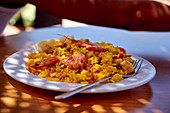Paella with prawns on a table outside
