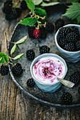 Brombeerjoghurt und frische Brombeeren in Schälchen