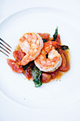 Roasted king prawns on cherry tomatoes with basil