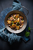 Fried potatoes with mushrooms and red onions in a serving pan