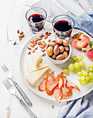 Wine snack set - Cheese, chicken carpaccio, mediterranean olives, fruits, nuts and two glasses of red wine