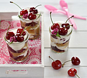 Vegan cherry and caramel dessert in glasses with caramel biscuits, almond yoghurt, caramel cream and cherry compote