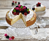 Vegan lemon sponge cheesecake with a baked quark layer decorated with soy cream, raspberries and blackberries