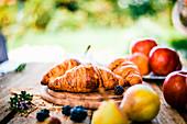 Frische Croissants und frische Früchte auf Holztisch