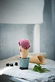 Vegan blackberry ice cream in a cone