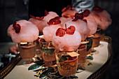 Mit Zuckerwatte und Begonienblüten garnierte Cocktails