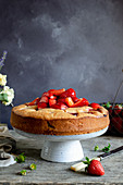 Strawberry cake on the cakestand, topped with fresh strawberries